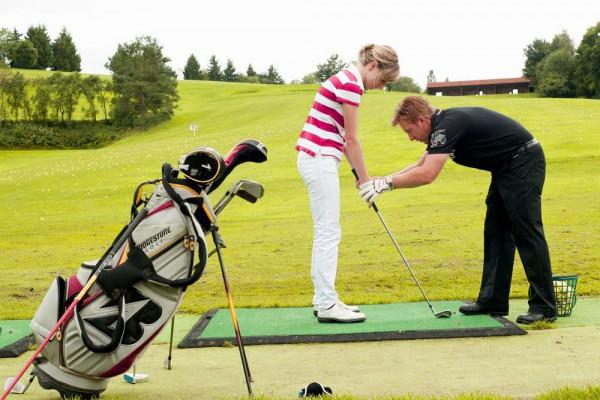 Golfpro mit Schüler_farb